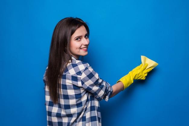 Positieve vrouw reiniger in rubberen handschoenen venster met spons en reinigingsmiddel schoonmaken. schoonmaak concept