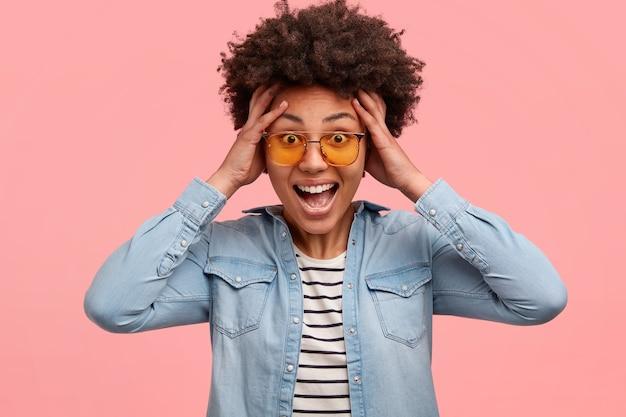 Positieve vrouw van gemengd ras houdt de handen op het hoofd, heeft een afro-kapsel, ontvangt een ongelooflijke verrassing