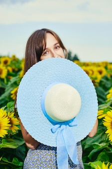 Positieve vrouw verbergt zichzelf met blauwe breedgerande hoed