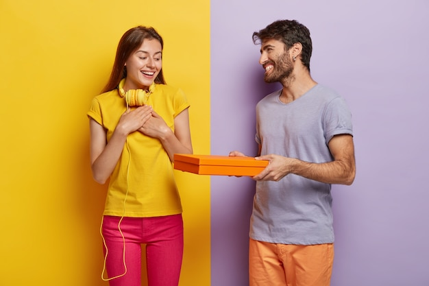 Positieve vrouw voelt dankbaarheid voor het ontvangen van een vriendje, drukt goede emoties uit. zorgzame man geeft kartonnen doos met verrassing aan zijn vriendin, komt feliciteren met verjaardag