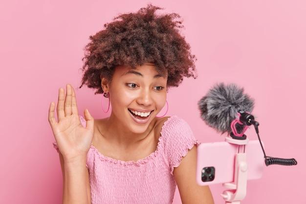 Positieve vrouwelijke blogger met afro-haar praat met volgers tijdens live streaming golven hallo begroet abonnees poses voor smartphone camera
