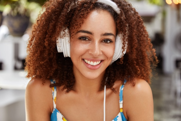 Positieve vrouwelijke blogger met donkere huid en afro-kapsel recreëert buiten tijdens het luisteren naar favoriete muziek, verbonden met een mobiele telefoon