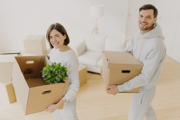 Positieve vrouwelijke en mannelijke huiseigenaren poseren met persoonlijke bezittingen in kartonnen dozen, verhuizing