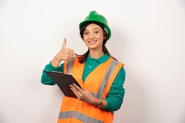 Positieve vrouwelijke industrieel ingenieur in uniform met klembord op witte achtergrond.