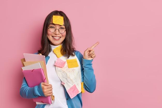 Positieve vrouwelijke kantoormedewerker met mappen en stickers draagt ronde bril en blauwe jumper wijst weg op kopie ruimte geeft aanbeveling hoe voor te bereiden succesvol project maakt presentatie