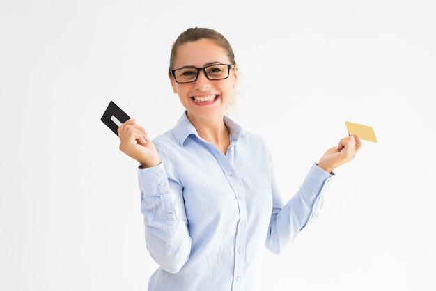 Positieve vrouwelijke klant die verscheidene loyaliteitskaarten houdt