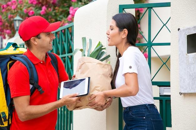 Positieve vrouwelijke klant die voedsel ontvangt van de supermarkt en het pakket neemt van de koerier bij haar gate. verzending of levering dienstverleningsconcept