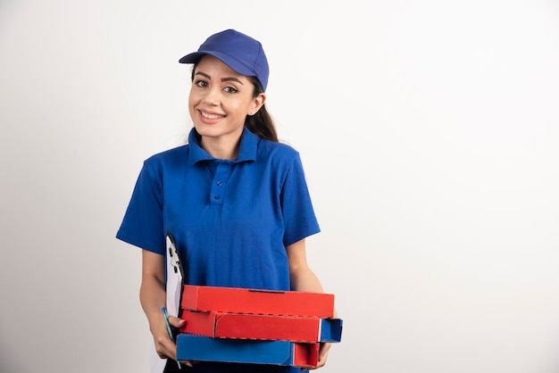 Positieve vrouwelijke koerier met karton van pizza en klembord