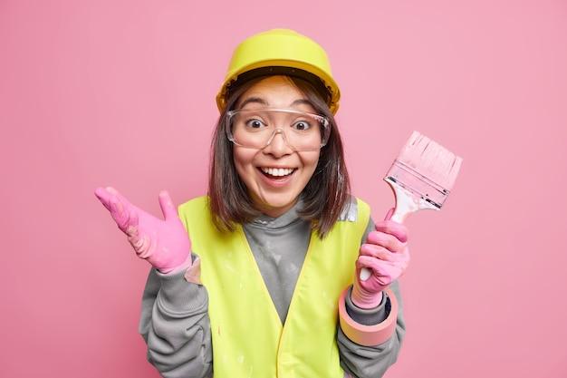 Positieve vrouwelijke onderhoudsmedewerker met schilderborstel