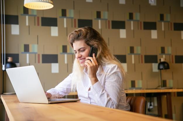 Positieve vrouwelijke ondernemer die op laptop werkt en op celtelefoon in co-werkruimte spreekt
