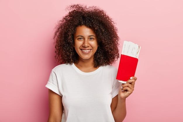 Positieve vrouwelijke passagier houdt instapkaart tickets en paspoort, bereidt zich voor op vliegreizen vlucht, geniet van reizen, heeft een krullend kapsel, draagt een wit t-shirt, glimlacht breed met perfecte tanden