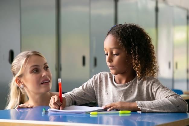 Positieve vrouwelijke schoolleraar die krullend haired meisje helpt om haar taak te doen
