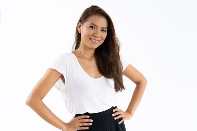 Positieve vrouwelijke student die het witte t-shirt stellen bij camera draagt