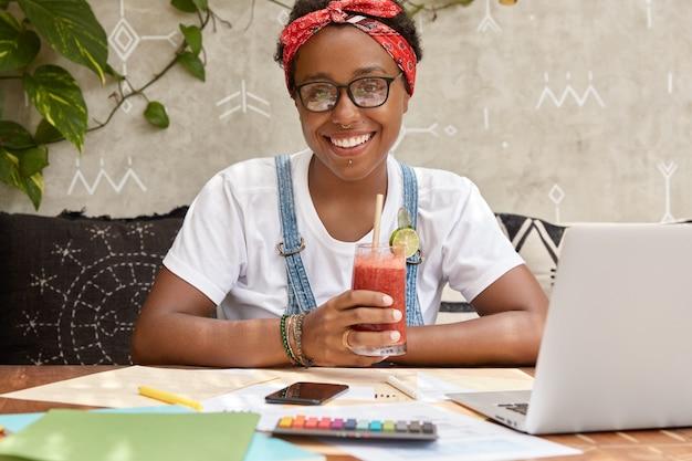 Positieve vrouwelijke toerismewerker ontwikkelt website van reisbureau, onderzoekt financiële kant