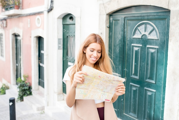 Positieve vrouwelijke toerist die document kaart op straat gebruikt