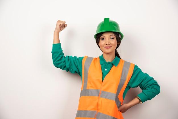 Positieve vrouwelijke werknemer die haar spieren toont Gratis Foto