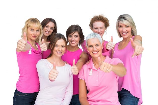 Positieve vrouwen die en roze voor borstkanker stellen dragen