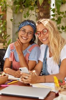 Positieve vrouwen van gemengd ras chatten op de mobiele telefoon, gebruiken een internetverbinding