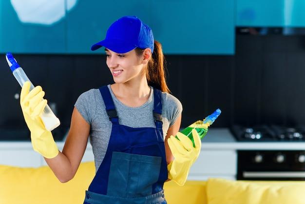 Positieve werkneemster van professionele schoonmaak maakt een keuze tussen verschillende schoonmaakmiddelen op de achtergrond van de moderne keuken. huis schoonmaak dienstverleningsconcept.