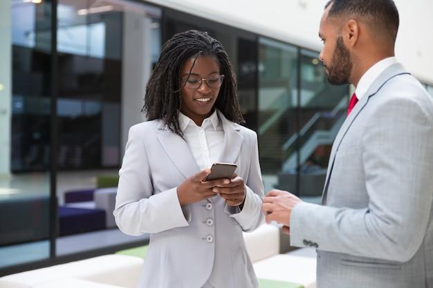 Positieve zakelijke collega's met behulp van mobiele telefoons