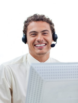 Positieve zakenman die op hoofdtelefoon bij een computer spreekt