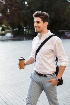 Positieve zakenman gekleed in overhemd lopen