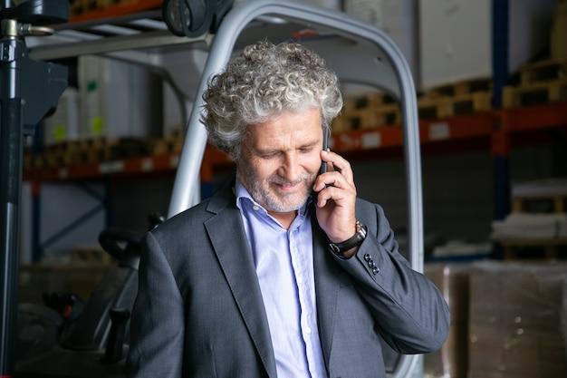 Positieve zakenman permanent in de buurt van heftruck in magazijn en praten over mobiel. planken met goederen op achtergrond. bedrijfs- of logistiek concept