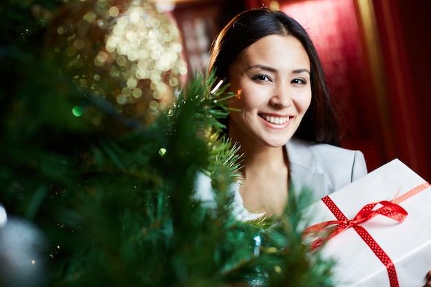 Positieve zakenvrouw in de buurt van de kerstboom