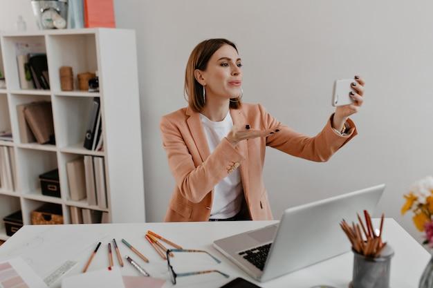 Positieve zakenvrouw in stijlvolle outfit stuurt luchtkus naar de camera van de telefoon terwijl ze op de werkplek zit.