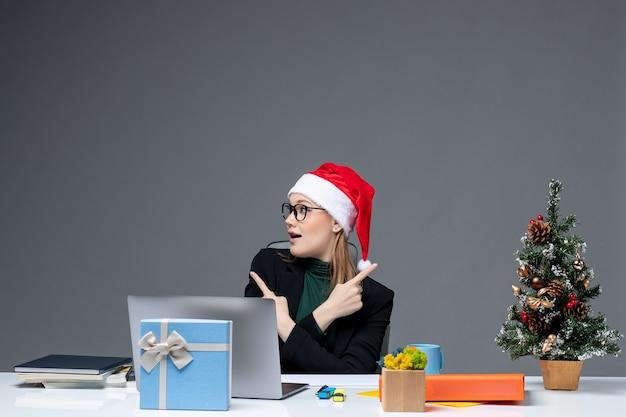 Positieve zakenvrouw met kerstman hoed zittend aan een tafel met een kerstboom en een cadeau erop op donkere achtergrond