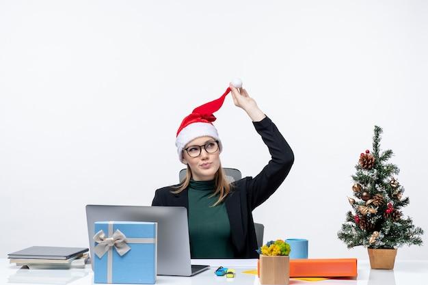 Positieve zakenvrouw spelen met haar kerstman hoed zittend aan een tafel met een kerstboom en een cadeau erop en gericht op iets op witte achtergrond