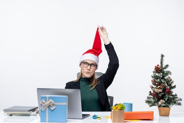 Positieve zakenvrouw spelen met haar kerstman hoed zittend aan een tafel met een kerstboom en een cadeau erop en na te denken over iets op witte achtergrond