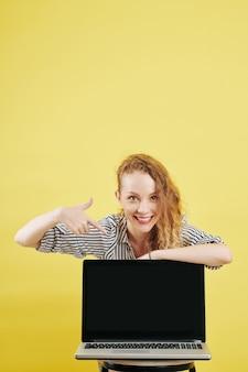 Positieve zakenvrouw wijzend op laptop scherm