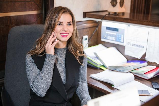 Positieve zelfverzekerde aantrekkelijke jonge receptioniste zittend aan tafel praten op mobiele telefoon