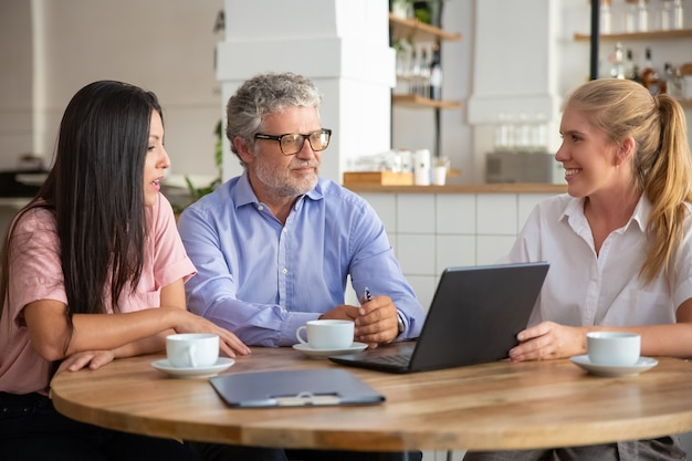 Positieve zelfverzekerde agent die projectpresentatie op laptop toont aan jonge en volwassen klanten