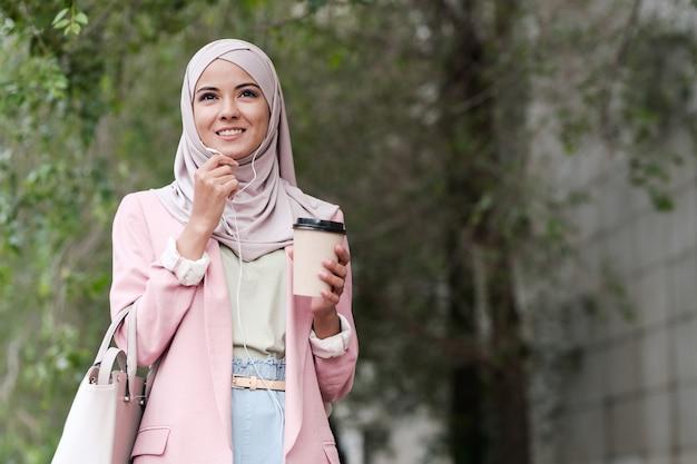 Positieve zelfverzekerde jonge moslim zakenvrouw in stijlvolle outfit afhaalmaaltijden koffie drinken en praten via telefoon headset buitenshuis