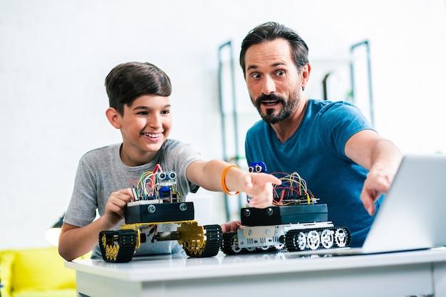 Positieve zoon en zijn vader gebruiken hun laptop terwijl ze experimenteren met hun robotapparaten
