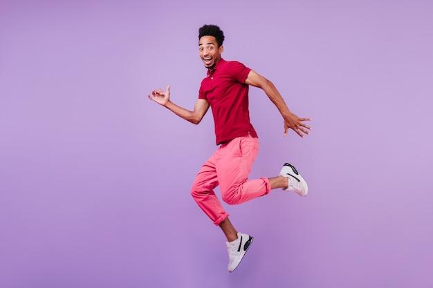 Positieve zorgeloze afrikaanse man in sportschoenen dansen. knappe blije man in roze broek springen met een glimlach.