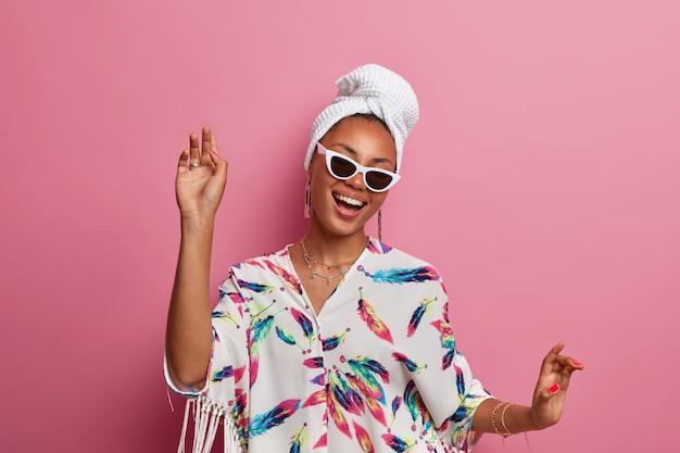 Positieve zorgeloze donkere jonge vrouw danst met vreugde heeft plezier gekleed in binnenlandse kamerjas draagt zonnebril en badhanddoek gewikkeld op hoofd geniet van het leven geïsoleerd over roze muur