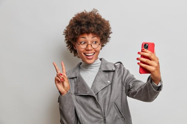 Positieve zorgeloze gekrulde harige vrouw neemt selfie op moderne smartphone, maakt vredesgebaar, heft twee vingers op, heeft een gelukkige uitdrukking, geniet van vrije tijd, gekleed in een stijlvol jasje
