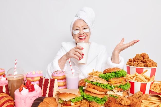 Positieve zorgeloze oude vrouw drinkt frisdrank omringd door junkfood