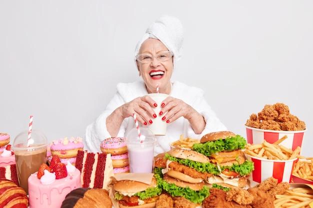 Positieve zorgeloze senior dame lacht breeduit drinkt frisdrank eet ongezond voedsel heeft een opgewekt humeur