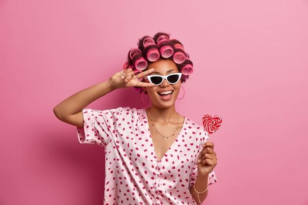 Positieve zorgeloze vrouw met donkere huid in trendy zonnebril maakt vredesgebaar over het oog, lacht vrolijk, heeft plezier, houdt lekkere lolly vast, draagt haarrollers voor het maken van perfecte krullen, nonchalant gekleed