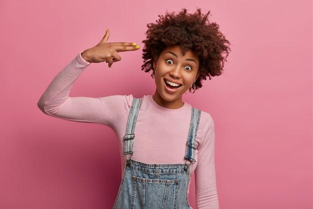Positieve zorgeloze vrouw schiet met vingerpistoolgebaar in de tempel, pleegt zelfmoord, dwazen rond, kijkt vrolijk, draagt denim overall en poloneck, geïsoleerd op roze pastel muur