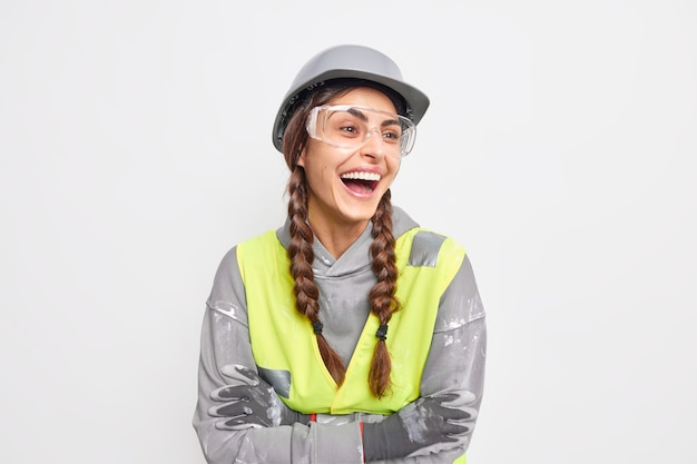 Positieve zorgeloze vrouwelijke ingenieur lacht vrolijk houdt de armen gevouwen en kijkt weg tevreden met snel bouwwerk
