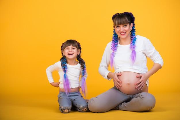 Positieve zwangere moeder en grappige dochter