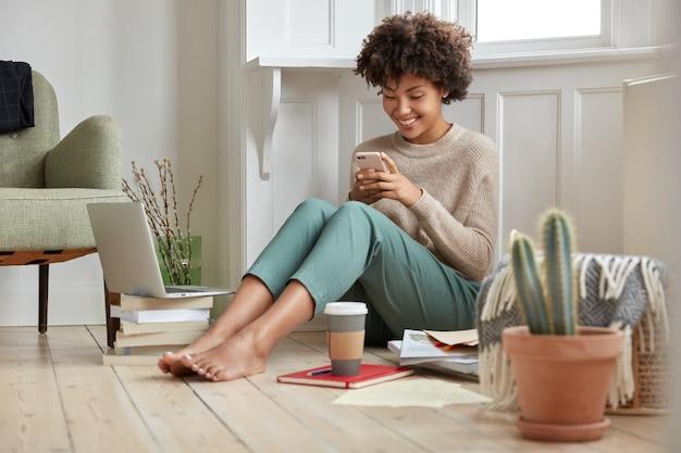 Positieve zwarte dame geniet van koffie om mee te nemen, houdt slimme telefoon in handen, leest sms-berichten in sociale netwerken, tevreden met moderne technologie en wifi-verbinding, studeert thuis binnenshuis, doet onderzoek