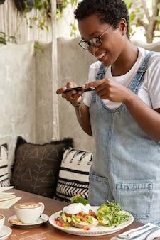 Positieve zwarte vrouw in jean sarafan