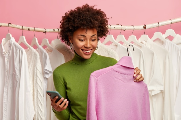 Positieve zwarte vrouw kiest trui om te kopen, houdt hanger met paarse coltrui vast, mobiele telefoon in andere hand