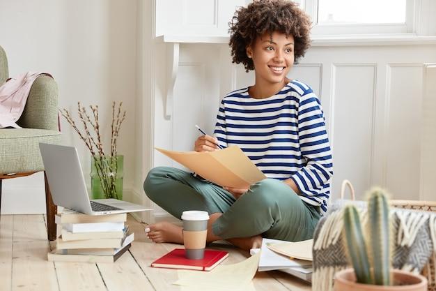 Positieve zwarte vrouw zit gekruiste benen, gekleed in gestreepte matrozen trui, houdt wat papieren bezig met het opstellen van een rapport